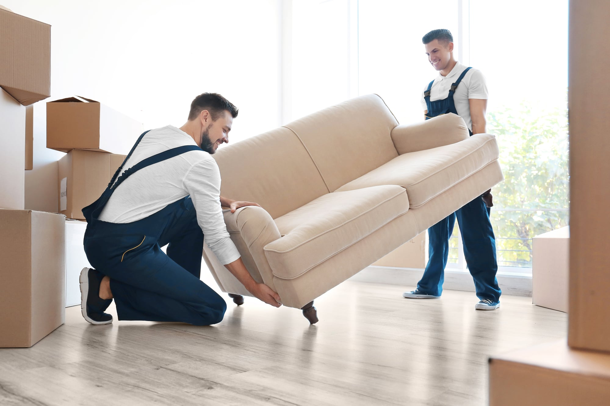 Professional movers lifting a sofa.